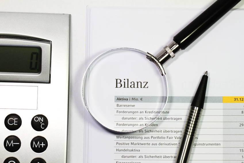 Bilanzseite mit Taschenrechner und Lupe