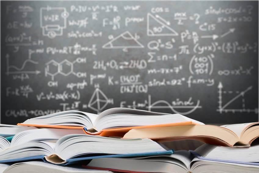 Bücher vor einer Tafel mit mathematischen Zeichen